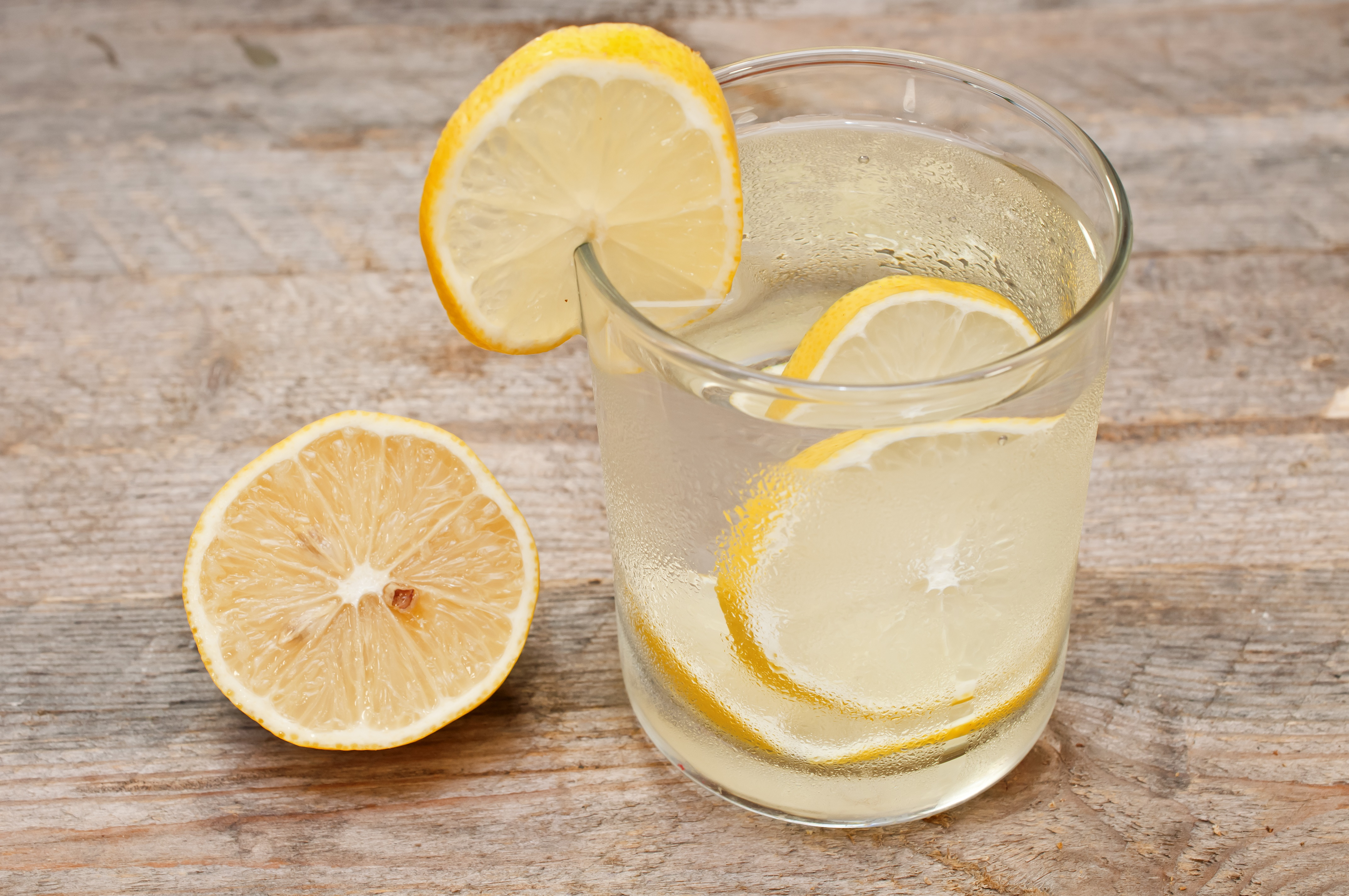 glass of water with lemon on the wooden table